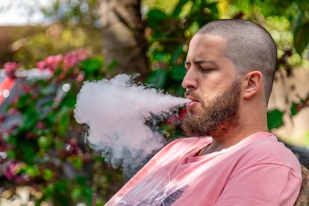Łysy i brodaty mężczyzna palenia.