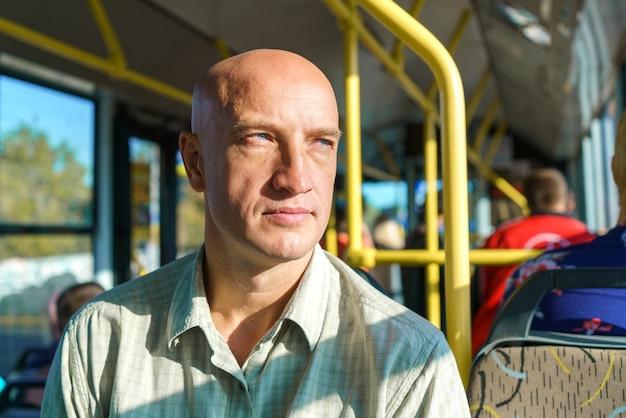 Łysy kaukaski mężczyzna jeździ komunikacją miejską, siedząc przy oknie w słoneczny, ciepły dzień, ciesz się ...
