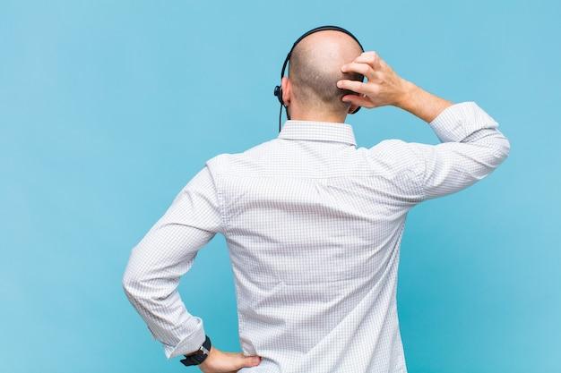 Łysy mężczyzna czuje się nieświadomy i zdezorientowany, myśląc o rozwiązaniu, z ręką na biodrze i drugą na głowie, widok z tyłu