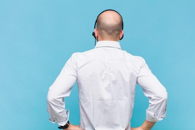 Łysy mężczyzna czuje się zagubiony lub pełny lub ma wątpliwości i pytania, zastanawiając się, z rękami na biodrach, widok z tyłu