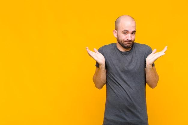 Łysy mężczyzna czuje się zdziwiony i zdezorientowany, wątpi, waży lub wybiera różne opcje z zabawnym wyrazem twarzy