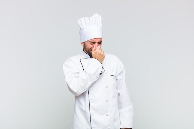 Łysy mężczyzna czuje się zniesmaczony, trzyma nos, aby uniknąć nieprzyjemnego zapachu