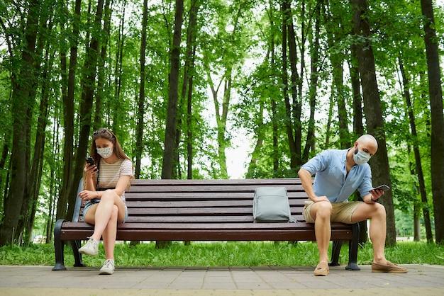 Łysy mężczyzna i młoda kobieta siedzą na ławce w odległości kilku metrów od siebie, aby uniknąć rozprzestrzeniania się koronawirusa.