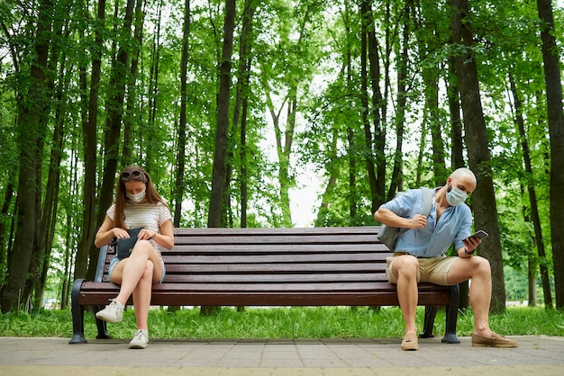 Łysy mężczyzna i młoda kobieta siedzą na przeciwległych końcach ławki, zachowując odległość od siebie, aby uniknąć rozprzestrzeniania się koronawirusa.