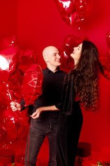 Łysy mężczyzna i młoda kobieta w czarnym stojaku z balonami w kształcie serca
