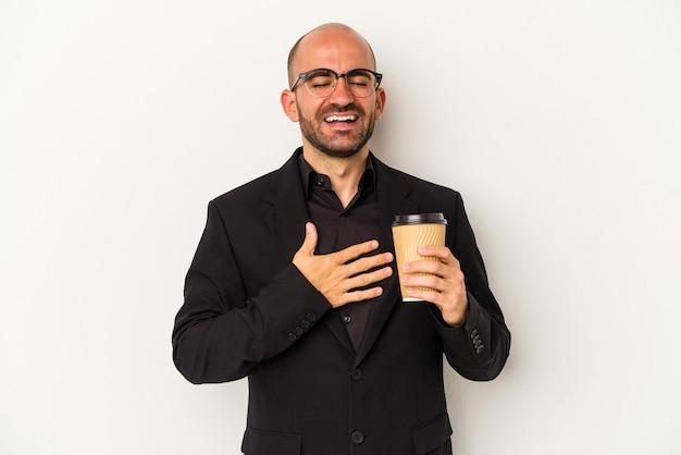Łysy mężczyzna młody biznes gospodarstwa zabrać kawę na białym tle śmieje się głośno trzymając rękę na klatce piersiowej.