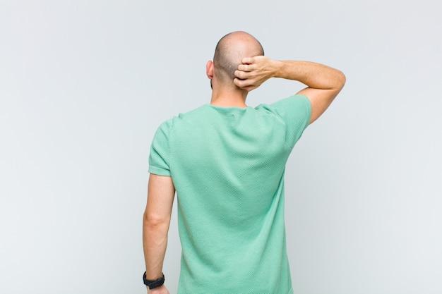 Łysy mężczyzna myśli lub wątpi, drapie się po głowie, czuje się zdziwiony i zdezorientowany, widok z tyłu lub z tyłu