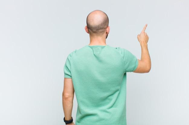 Łysy mężczyzna stojący i wskazując na obiekt
