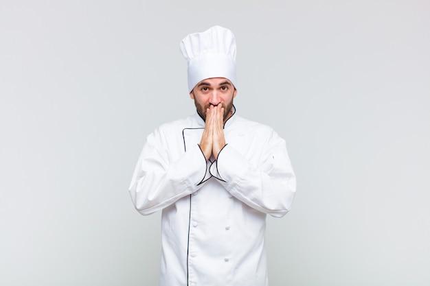 Łysy mężczyzna szczęśliwy i podekscytowany, zaskoczony i zdumiony zakrywający usta rękami, chichocząc z uroczym wyrazem twarzy