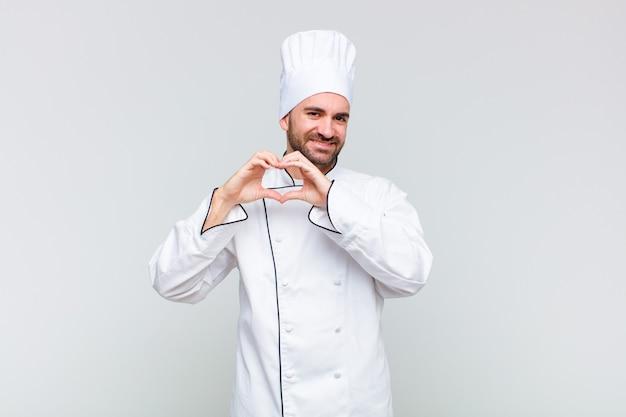 Łysy mężczyzna uśmiecha się i czuje się szczęśliwy, uroczy, romantyczny i zakochany, tworząc kształt serca obiema rękami