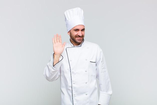 Łysy mężczyzna uśmiecha się radośnie i wesoło, macha ręką, wita i wita lub żegna
