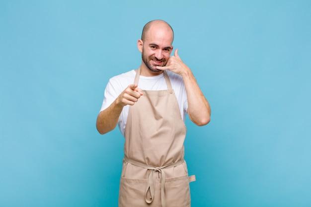 Łysy mężczyzna uśmiecha się radośnie i wskazuje na aparat, dzwoniąc do ciebie później gestem, rozmawiając przez telefon