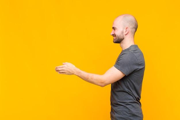 Łysy mężczyzna uśmiecha się, wita cię i oferuje uścisk dłoni, aby sfinalizować udaną transakcję