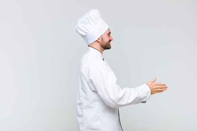 Łysy mężczyzna uśmiecha się, wita i oferuje uścisk dłoni, aby zamknąć udaną transakcję, koncepcja współpracy