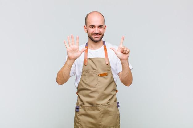 Łysy mężczyzna uśmiechnięty i wyglądający przyjaźnie, pokazujący numer siedem lub siódmy z ręką do przodu, odliczający