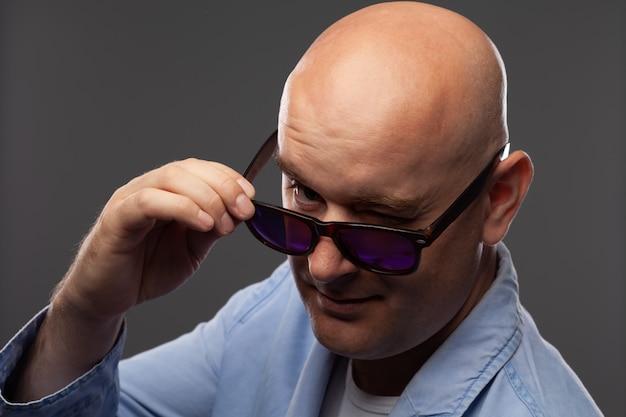 Łysy mężczyzna w czarnych okularach na szarej ścianie