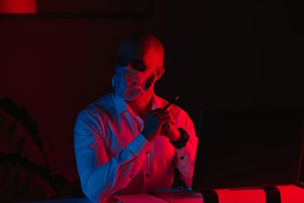 Łysy mężczyzna w masce medycznej pracuje zdalnie na laptopie w domu