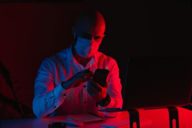 Łysy mężczyzna w medycznej masce na twarz pracuje zdalnie na laptopie w domu. facet czyta wiadomości na smartfonie. pracownik płci męskiej z piórem przed komputerem w świetle niebieskim i czerwonym.