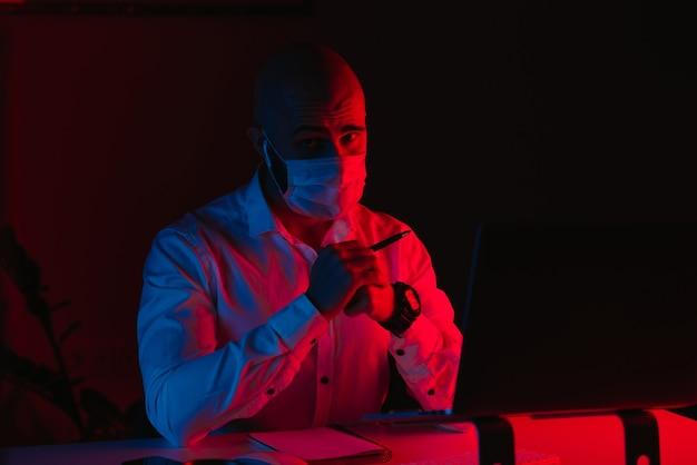 Łysy mężczyzna w medycznej masce na twarz pracuje zdalnie na laptopie w domu. facet się gapi. pracownik płci męskiej z piórem przed komputerem w świetle niebieskim i czerwonym.