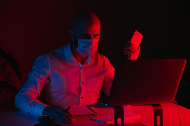 Łysy mężczyzna w medycznej masce na twarz pracuje zdalnie na laptopie w domu. facet ze słuchawkami trzyma telefon komórkowy. pracownik płci męskiej z piórem przed komputerem w świetle niebieskim i czerwonym.