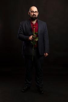 Łysy mężczyzna w okularach i brodą w garniturze z czerwoną różą w ręku.