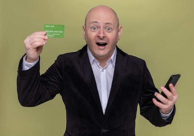 Łysy mężczyzna w średnim wieku w garniturze pokazuje zaskoczoną i szczęśliwą kartę kredytową stojącą nad zieloną ścianą