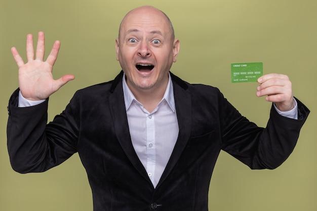Łysy mężczyzna w średnim wieku w garniturze przedstawiający kartę kredytową, która jest szczęśliwa i podekscytowana, pokazuje otwartą palmę numer pięć stojącą nad zieloną ścianą