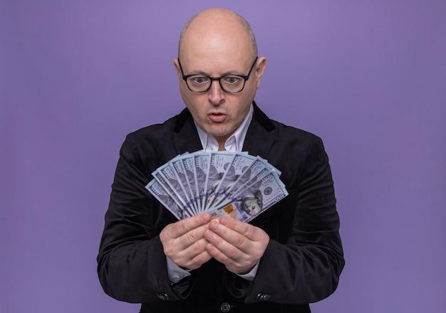 Łysy mężczyzna w średnim wieku w garniturze w okularach patrząc na pieniądze szczęśliwy i podekscytowany stojący