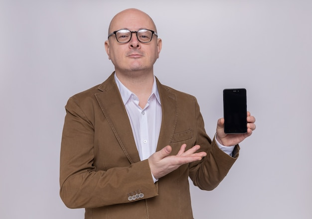 Łysy mężczyzna w średnim wieku w garniturze w okularach, prezentując smartfon patrząc na przód uśmiechnięty pewny siebie stojący nad białą ścianą