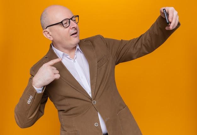 Łysy mężczyzna w średnim wieku w garniturze w okularach robi selfie przy użyciu smartfona szczęśliwy