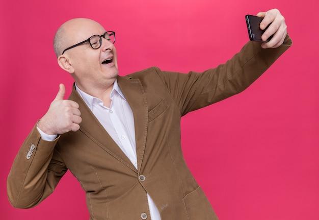 Łysy mężczyzna w średnim wieku w garniturze w okularach robi selfie za pomocą smartfona, uśmiechając się radośnie pokazując kciuki do góry stojąc nad różową ścianą