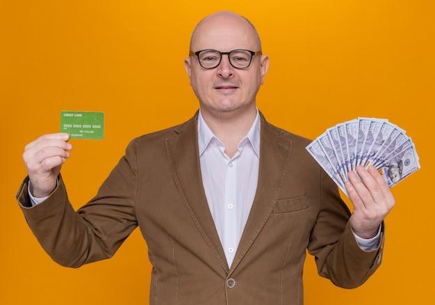 Łysy mężczyzna w średnim wieku w garniturze w okularach, trzymając gotówkę i kartę kredytową, patrząc na kamery szczęśliwy
