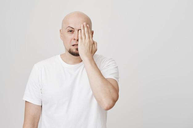 Łysy mężczyzna w średnim wieku zasłania jedno oko, sprawdzając wzrok u optyka