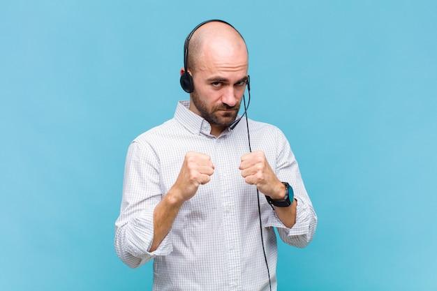 Łysy mężczyzna wyglądający na pewnego siebie, wściekłego, silnego i agresywnego, z pięściami gotowymi do walki w pozycji bokserskiej