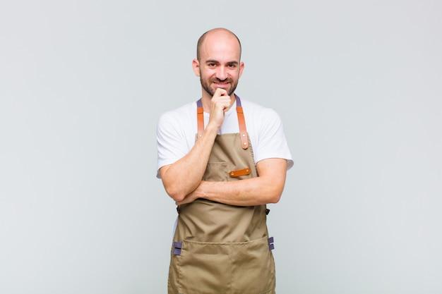 Łysy mężczyzna wyglądający na szczęśliwego i uśmiechniętego z ręką na brodzie, zastanawiający się lub zadający pytanie, porównujący opcje