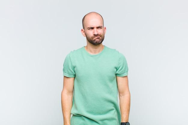 Łysy mężczyzna wyglądający na zdziwionego i zdezorientowanego, zastanawiający się lub próbujący rozwiązać problem lub myślący
