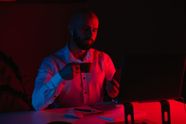 Łysy mężczyzna z brodą pracuje zdalnie na laptopie w domu
