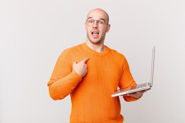 Łysy mężczyzna z komputerem czujący się szczęśliwy, zaskoczony i dumny, wskazujący na siebie z podekscytowanym, zdumionym spojrzeniem