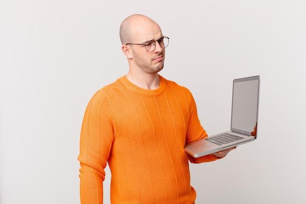 Łysy mężczyzna z komputerem czuje się smutny, zdenerwowany lub zły i patrzy w bok z negatywnym nastawieniem, marszcząc brwi w niezgodzie