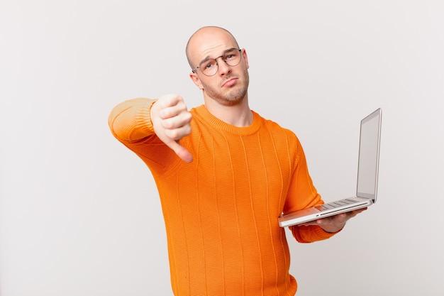 Łysy mężczyzna z komputerem czuje się zły, zły, zirytowany, rozczarowany lub niezadowolony, pokazując kciuk w dół z poważnym spojrzeniem
