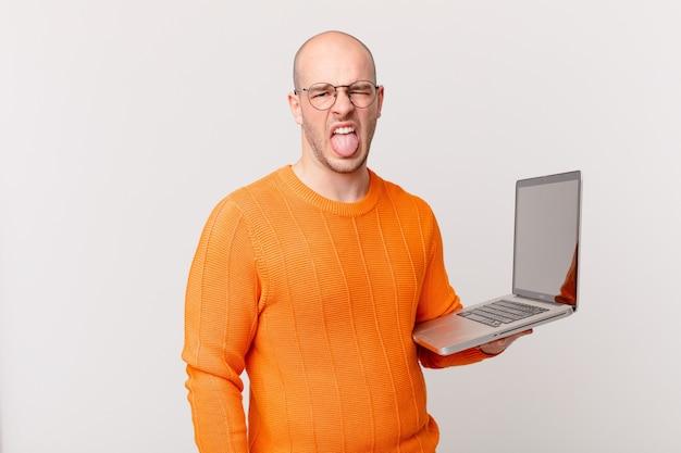 Łysy mężczyzna z komputerem czuje się zniesmaczony i zirytowany, wysuwa język, nie lubi czegoś paskudnego i obrzydliwego