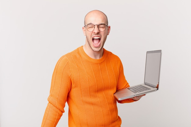 """Łysy mężczyzna z komputerem krzyczy agresywnie, wygląda na bardzo rozgniewanego, sfrustrowanego, oburzonego lub zirytowanego, krzyczy """"nie"""""""