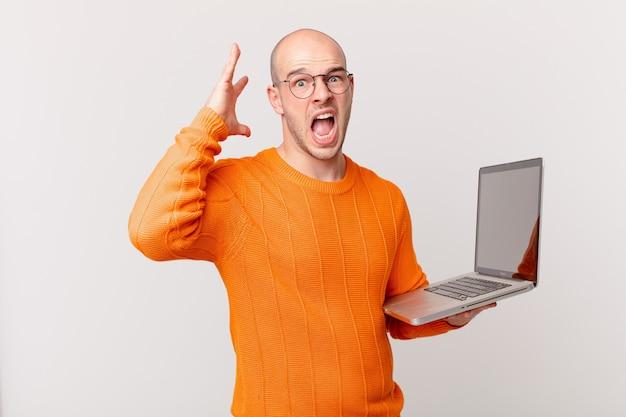 Łysy mężczyzna z komputerem krzyczy z rękami w górze, czuje się wściekły, sfrustrowany, zestresowany i zdenerwowany