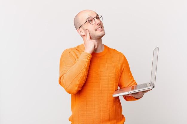 Łysy mężczyzna z komputerem uśmiecha się radośnie i marzy lub wątpi, patrząc w bok