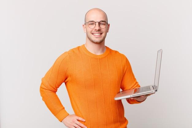 Łysy mężczyzna z komputerem uśmiechający się radośnie z ręką na biodrze i pewny siebie, pozytywny, dumny i przyjazny