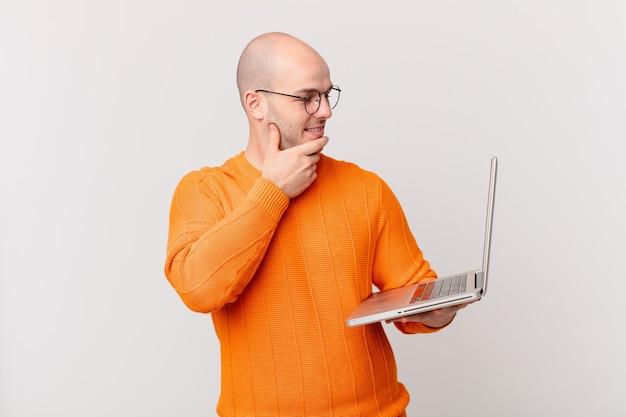 Łysy mężczyzna z komputerem uśmiechający się ze szczęśliwym, pewnym siebie wyrazem twarzy z ręką na brodzie, zastanawiający się i patrzący w bok