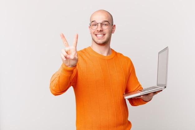 Łysy mężczyzna z komputerem uśmiechnięty i wyglądający na szczęśliwego, beztroskiego i pozytywnego, gestykulujący jedną ręką zwycięstwo lub pokój