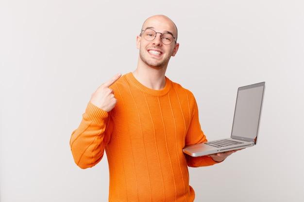 Łysy mężczyzna z komputerem uśmiechnięty pewnie wskazujący na swój szeroki uśmiech, pozytywne, zrelaksowane, zadowolone nastawienie