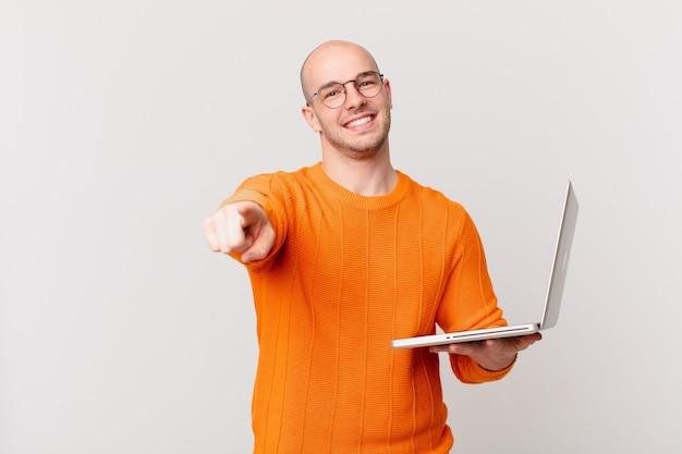 Łysy mężczyzna z komputerem wskazującym na aparat z zadowolonym, pewnym siebie, przyjaznym uśmiechem, wybierający ciebie