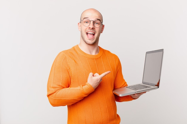 Łysy mężczyzna z komputerem wygląda na podekscytowanego i zdziwionego, wskazując na bok i w górę, aby skopiować przestrzeń